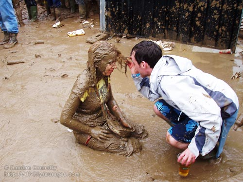 A woman sitting in a pool of mud at Oxegen 2007