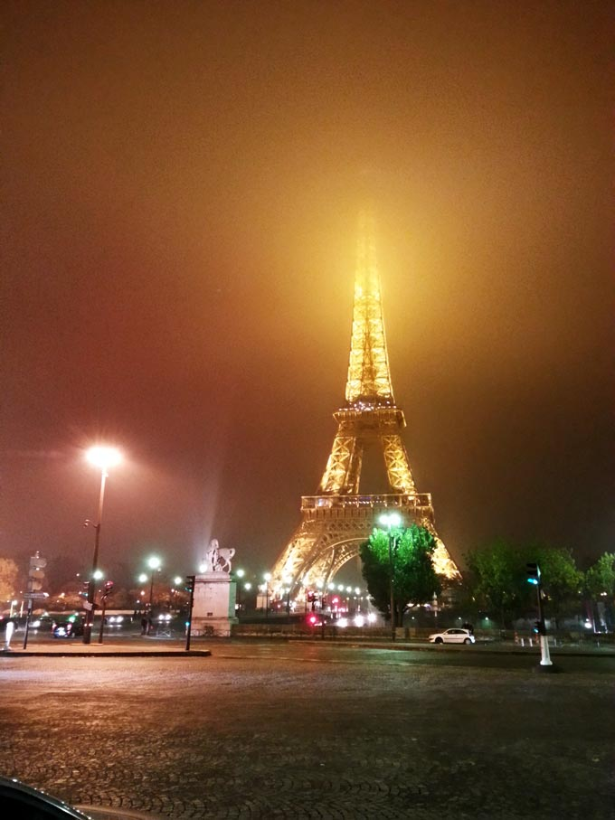 The Eiffel Tower, from a distance, on a foggy night